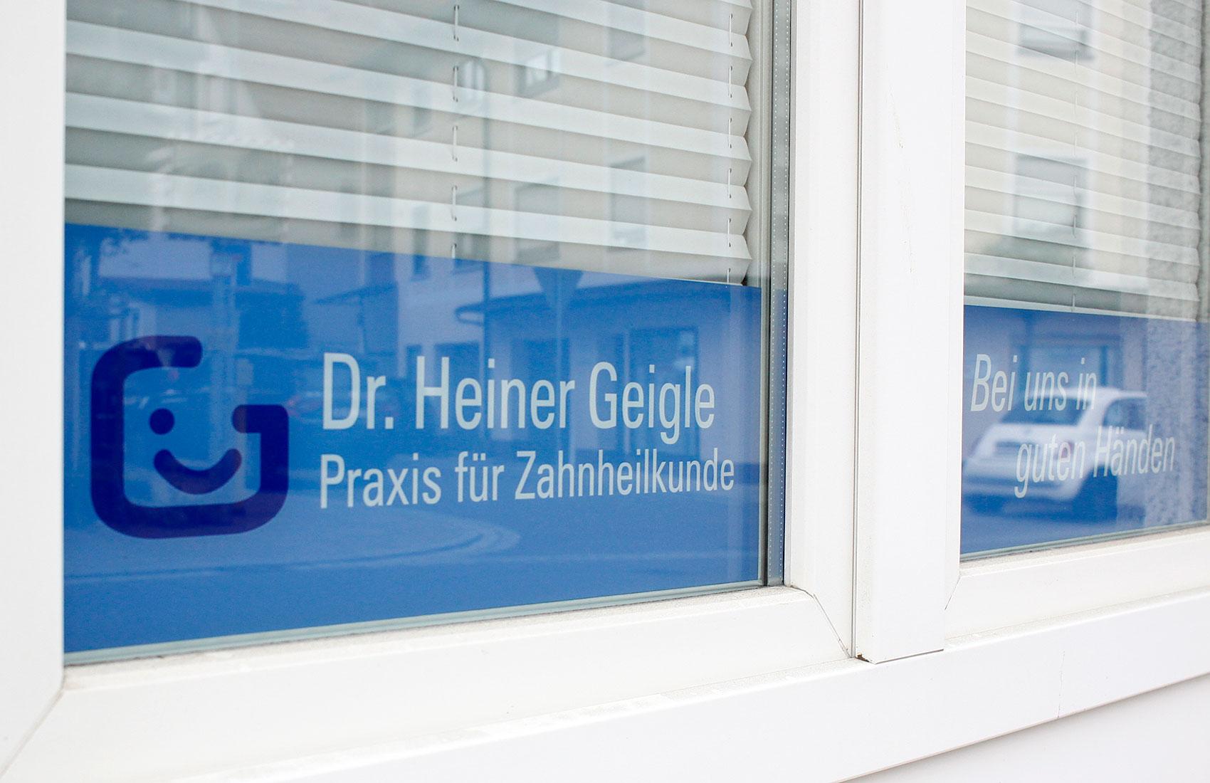 Folienbeschriftungen an den Fenstern (Fensterbeklebung) kommunizieren Telefonnummer, Webadresse, Logo und Slogan der Zahnarztpraxis.