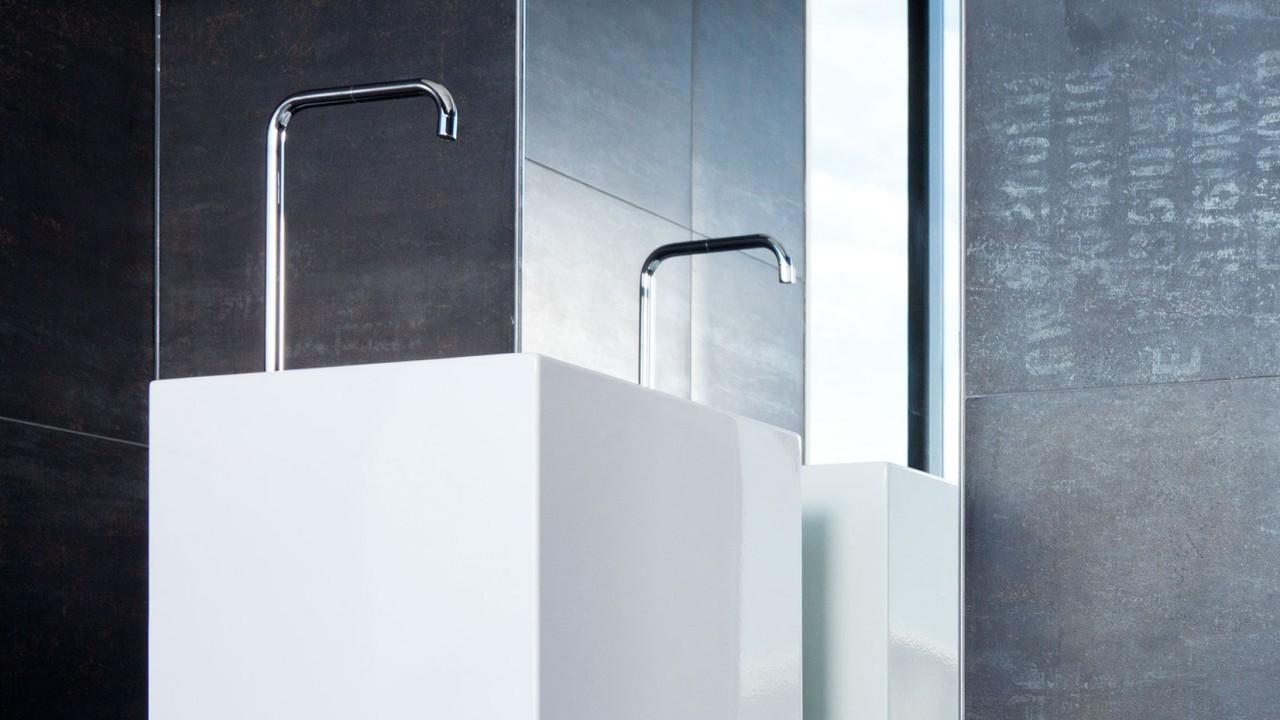 Waschbecken wie ein eckiger Sockel mit einer hohen Armatur