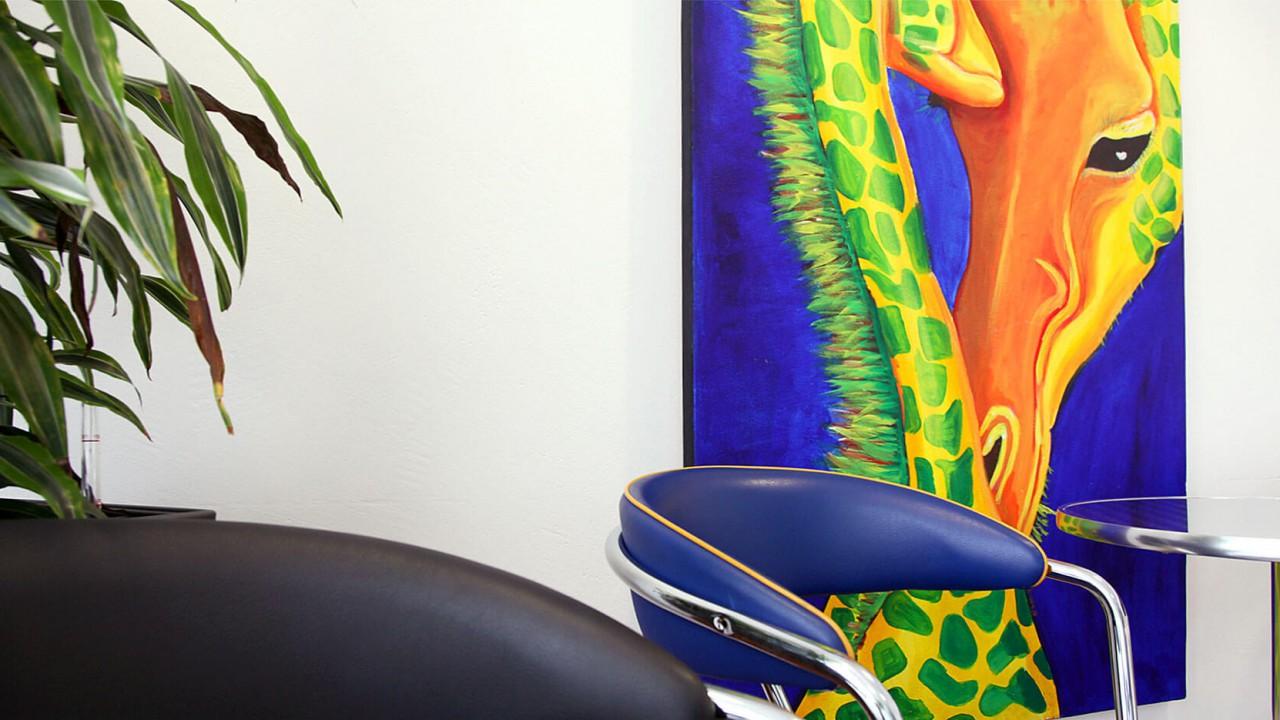 Im Wartezimmer hängt ein Bild von bunten Giraffen