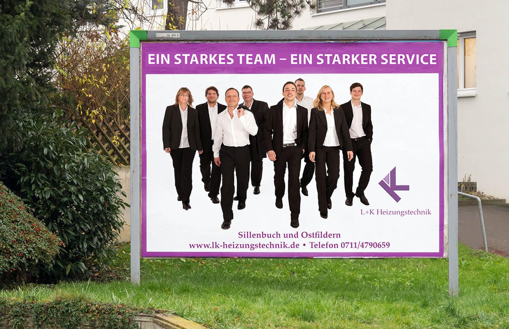 Das Teamfoto wird zu Werbezwecken auf einem Großflächenplakat verwendet