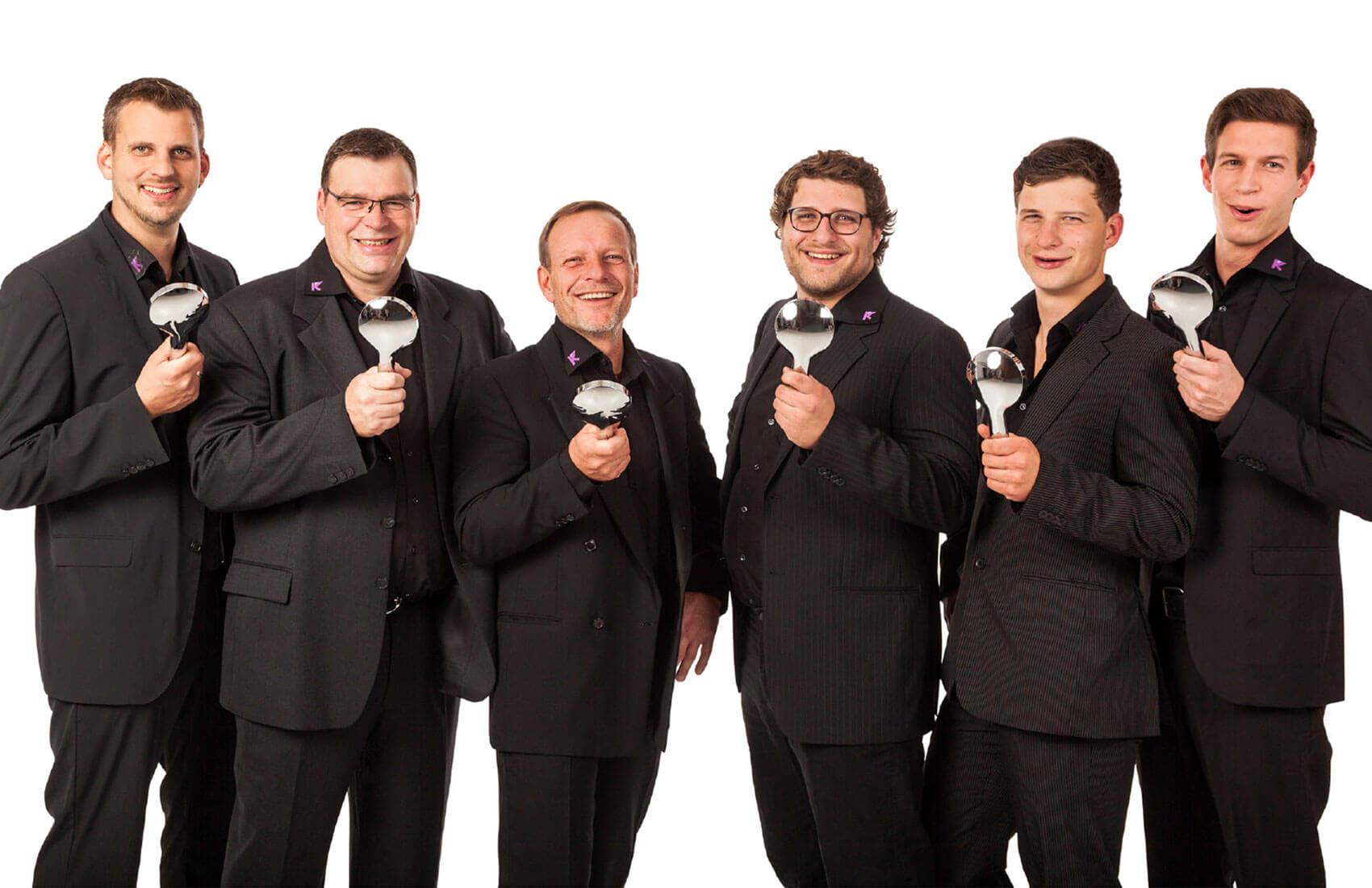 """Teamfoto als Weihnachtsmotiv: alle Herren """"singen"""" mit einem Duschkopf als Mikrophon"""